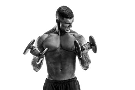 Studio portrait of handsome topless bodybuilder doing exercise on biceps against white background. Stock Photo