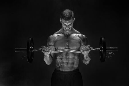Studio portrait of bodybuilder performing biceps exercise with concentrated face over black background with smoke. Cutout. Very brawny guy bodybuilder. Stock Photo