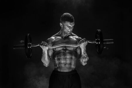 Studio portrait of bodybuilder performing biceps exercise with concentrated face over black background with smoke. Cutout. Very brawny guy bodybuilder.