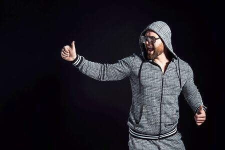 man in a grey suit with a hood in disco glasses against a dark background in the studio. Isolate