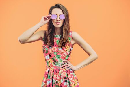Girl in floral dress emotionally poses on the orange background.