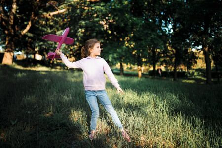 Little girl launches a toy plane into the air in the park outdoor. Child launches a toy plane. Beautiful little girl stands on the grass and launches a pink toy plane. 写真素材
