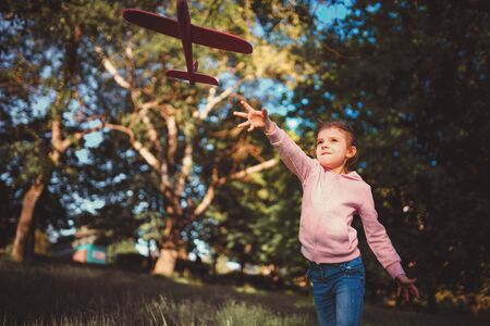 Little girl launches a toy plane into the air in the park outdoor. Child launches a toy plane. Beautiful little girl stands on the grass and launches a pink toy plane. 写真素材 - 138000227