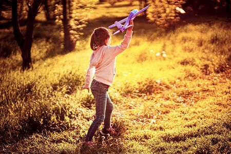 Little girl launches a toy plane into the air in the park outdoor. Child launches a toy plane. Beautiful little girl stands on the grass and launches a pink toy plane. Archivio Fotografico