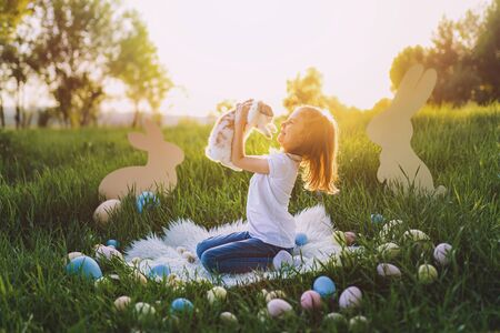 little girl holding cute fluffy Bunny. Friendship with Easter Bunny. Spring photo with beautiful young girl with her Bunny. Girl is holding a cute little rabbit.