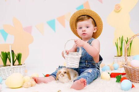 Happy little boy in hat holding cute fluffy Bunny. Friendship with Easter Bunny. Spring photo with little boy with his Bunny. boy is holding a cute little rabbit.