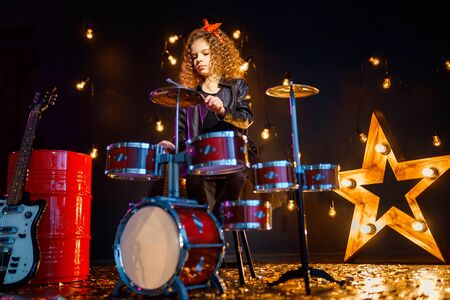 Beautiful girl with curly hair playing the drums on a black illuminated background