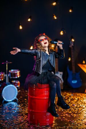 Beautiful girl with curly hair wearing leather jacket, red sunglasses sing into a wireless microphone for karaoke while sitting on red tank in recording studio or stage.