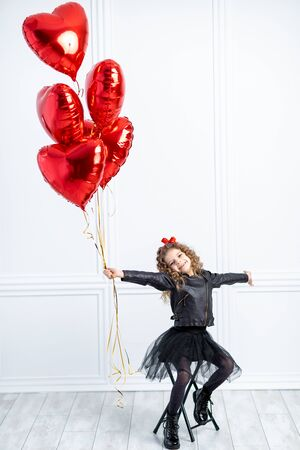 Valentine Beauty young girl, teenager with red air balloon portrait, isolated on background. Beautiful Happy Young kid holding balloons. Holiday party, birthday. Joyful little model. 写真素材