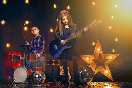 Kids pretending to be in a rock band and play and sing at studio or stage.
