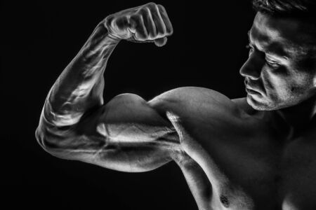 Strong Athletic Sexy Muscular Man on Black Background showing biceps. Black and White color tone.