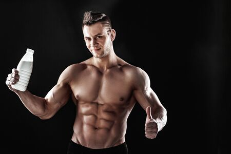 sexy muscular male torso and body of handsome macho man or athlete guy workout or training, holds white thermo mug, bottle or flask with drink on black background.