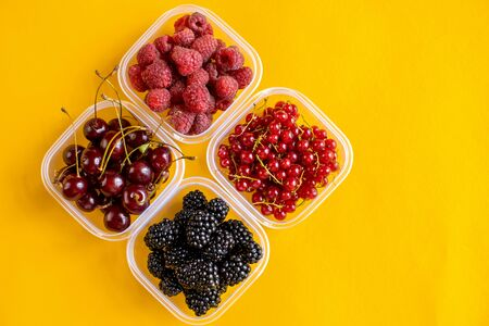 4 plastic plates, containers with raspberry, blackberry, red currant, cherry on a yellow background. 写真素材
