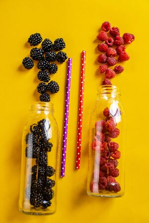 Blackberry and raspberry fruit in glass bottles with straws on yellow background. Fresh organic Smoothie ingredients. Superfoods and health or detox diet food concept. Isolate