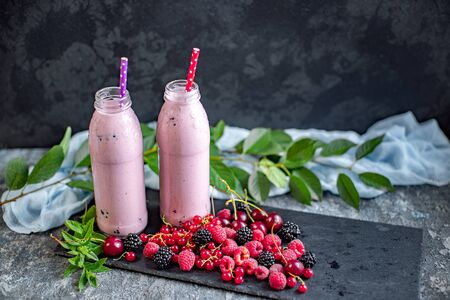2 jars of milkshake or smoothie with cranberries, strawberries and blueberries standing on stone backdrop.