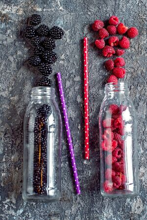 Blackberry and raspberry fruit in glass bottles with straws on stone background. Fresh organic Smoothie ingredients. Superfoods and health or detox diet food concept. 写真素材