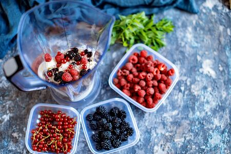 Blender with oatmeal, plastic plates, containers with raspberry, blackberry, red currant, cherry on a stone background. Making a healthy smoothie on a blender.