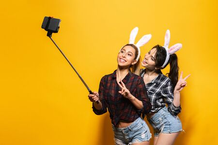 Two Young sexy caucasian woman wearing cute easter rabbit ears making selfie using stick over yellow isolated background.