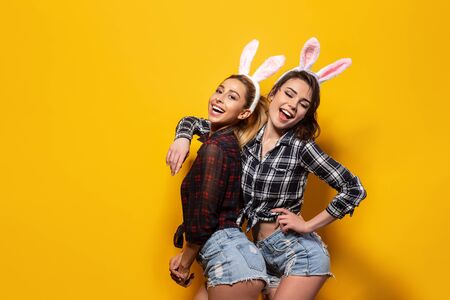 Two Young sexy caucasian woman wearing cute easter rabbit ears over yellow isolated background smiling.