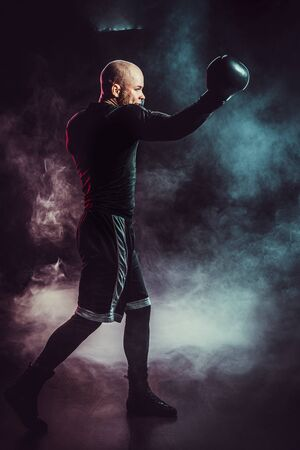 Sportsman boxer fighting on black background with smoke. Boxing sport concept. 写真素材
