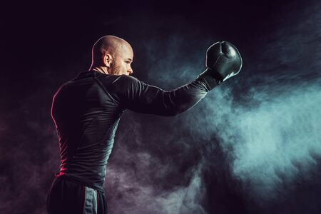 Sportsman boxer fighting, hitting uppercut on black background with smoke. Boxing sport concept.