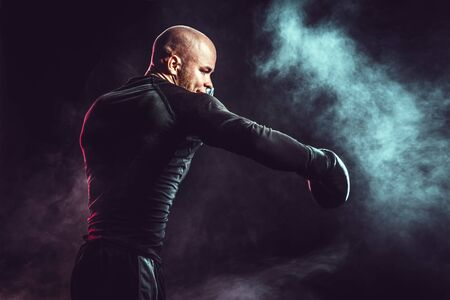 Sportsman boxer fighting, hitting side impact on black background with smoke. Boxing sport concept.