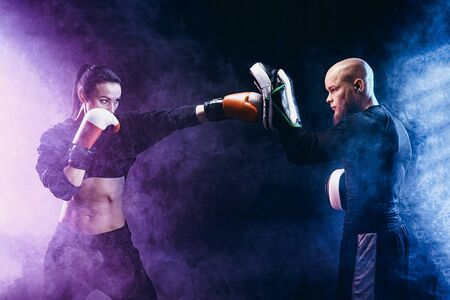 Woman exercising with trainer at boxing and self defense lesson, studio, smoke on background. Stock Photo