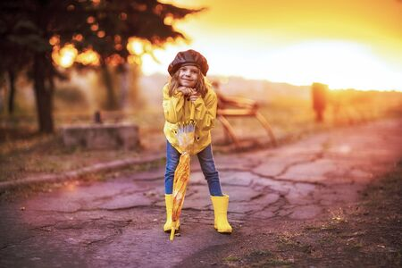 Happy funny child girl with umbrella in rubber boots at autumn park at sunset