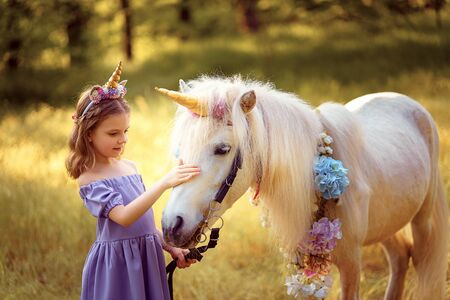 Girl in purple dress with wreath of a unicorn in hair hugging and kissing white unicorn. Dreams come true. Fairy tale. Фото со стока