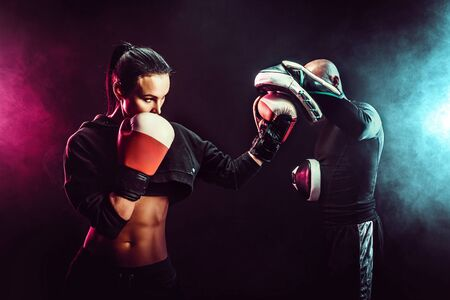 Woman exercising with trainer at boxing and self defense lesson, studio, smoke on background. 写真素材