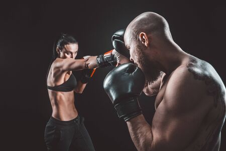Shirtless Woman exercising with trainer at boxing and self defense lesson, studio, smoke on background. Female and male fight,