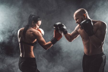Shirtless Woman exercising with trainer at boxing and self defense lesson, studio, dark background. Female and male fight. Archivio Fotografico