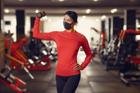 Coronavirus covid-19 prevention, fitness girl with a medical mask holding a dumbbell . Fighting viruses. Stock Photo