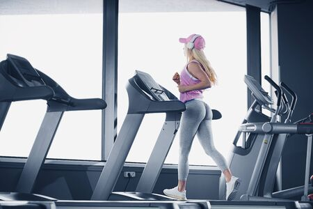Side view of sporty blonde woman in pink cap exercising on treadmill in gym. Stock Photo