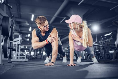 Man and woman strengthen hands at fitness training. Fitness young people doing pushups in a gym looking face happy exercise