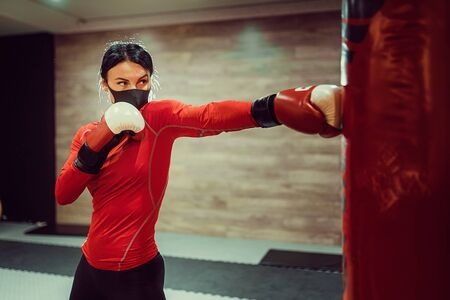Coronavirus covid-19 prevention, fight. Girl with a medical mask and boxing gloves. Fighting viruses.