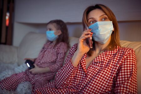 Woman with Little kid at home isolation auto quarantine wearing face mask with smart phone for reading information about Coronavirus Disease 2019.