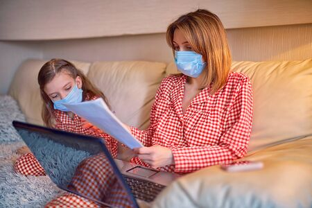 Woman in pajamas with notebook and papers working from home wearing protective mask while her kid, daughter playing computer console games.