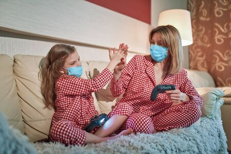 Woman and young girl wearing pajamas and medical protective masks sitting on sofa in living room with video game controllers at home isolation auto quarantine, covid-19. Imagens
