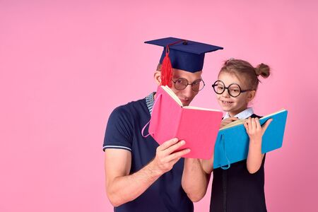 Man in academic hat holding book, study together with cute preteen girl in school uniform. Father, daughter isolated on pink background in studio. Love family day parenthood childhood concept.