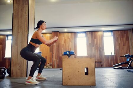 Shot of young woman working out with a box at the gym. Female athlete box jumping at a crossfit gym.