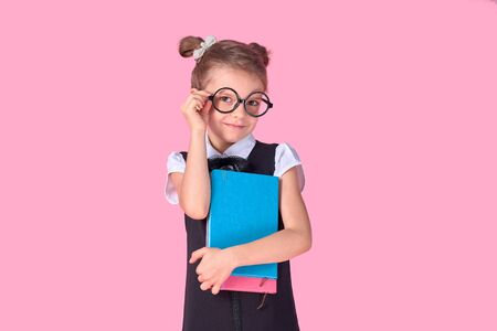 Cute little girl with glasses and books on pink background, space for text. Reading concept. 免版税图像