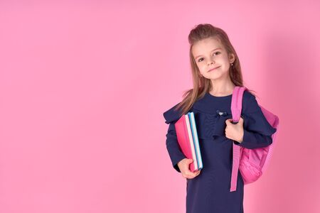 Back to school concept Half turned photo portrait of lovely confident beautiful clever girl with copybook notebook wearing school uniform dress pink bright backpack isolated.
