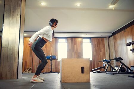 Shot of young woman working out with a box at the gym. Female athlete box jumping at a functional training gym.