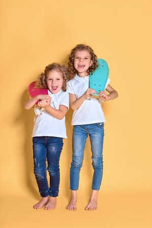Two Active and happy girls with curly hair having fun with penny board, smiling face stand skateboard. Penny board cute skateboard for girls. Lets ride. Girl with penny board yellow background. Stock Photo