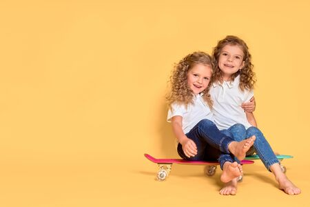 Two Active and happy girls with curly hair having fun with penny board, smiling face stand skateboard. Penny board cute skateboard for girls. Lets ride. Girl with penny board yellow background.