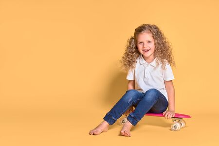 Active and happy girl with curly hair, headphones having fun with penny board, smiling face stand skateboard. Penny board cute skateboard for girls. Lets ride. Girl with penny board yellow background.