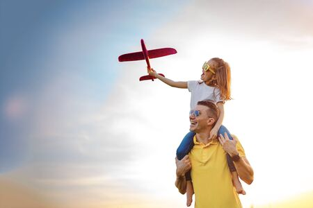 From below cheerful man smiling and carrying excited girl on shoulders while playing with red aircraft together against cloudy sky on sunny summer day