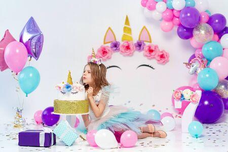 Unicorn Girl posing near happy birthday cake. Idea for decorating unicorn style birthday party. Unicorn decoration for festival party girl.