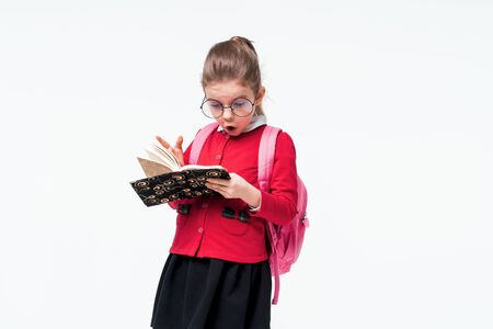 Adorable little girl in red school jacket, black dress, backpack and rounded glasses surprized or amazed looking at book while posing on white studio background. Isolate.